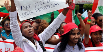 A MIGRANT DOMESTIC WORKER HOLDS A PLACARD DURING A MARCH DEMANDING BASIC LABOR RIGHTS AS LEBANESE WORKERS IN BEIRUT, LEBANON, MAY 3, 2015. CREDIT: AP PHOTO/BILAL HUSSEIN